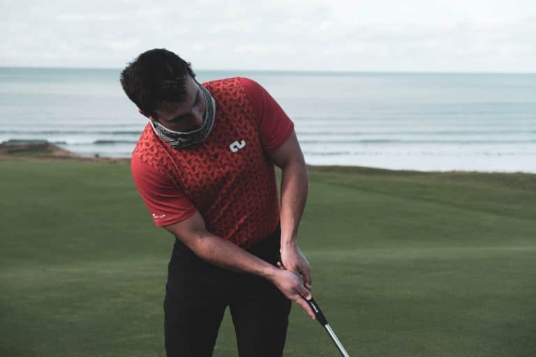 An image of a male golfer wearing a Low Profile Collar shirt and a fleece snood
