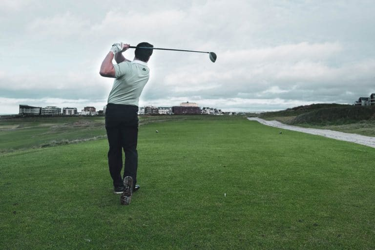 An image of a male golfer wearing one of our custom golf shirts.